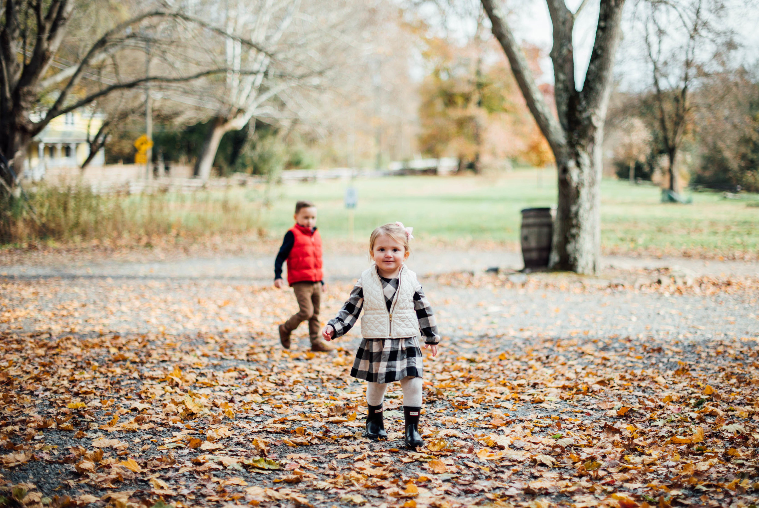 Little boy and girl running in the fall leaves
