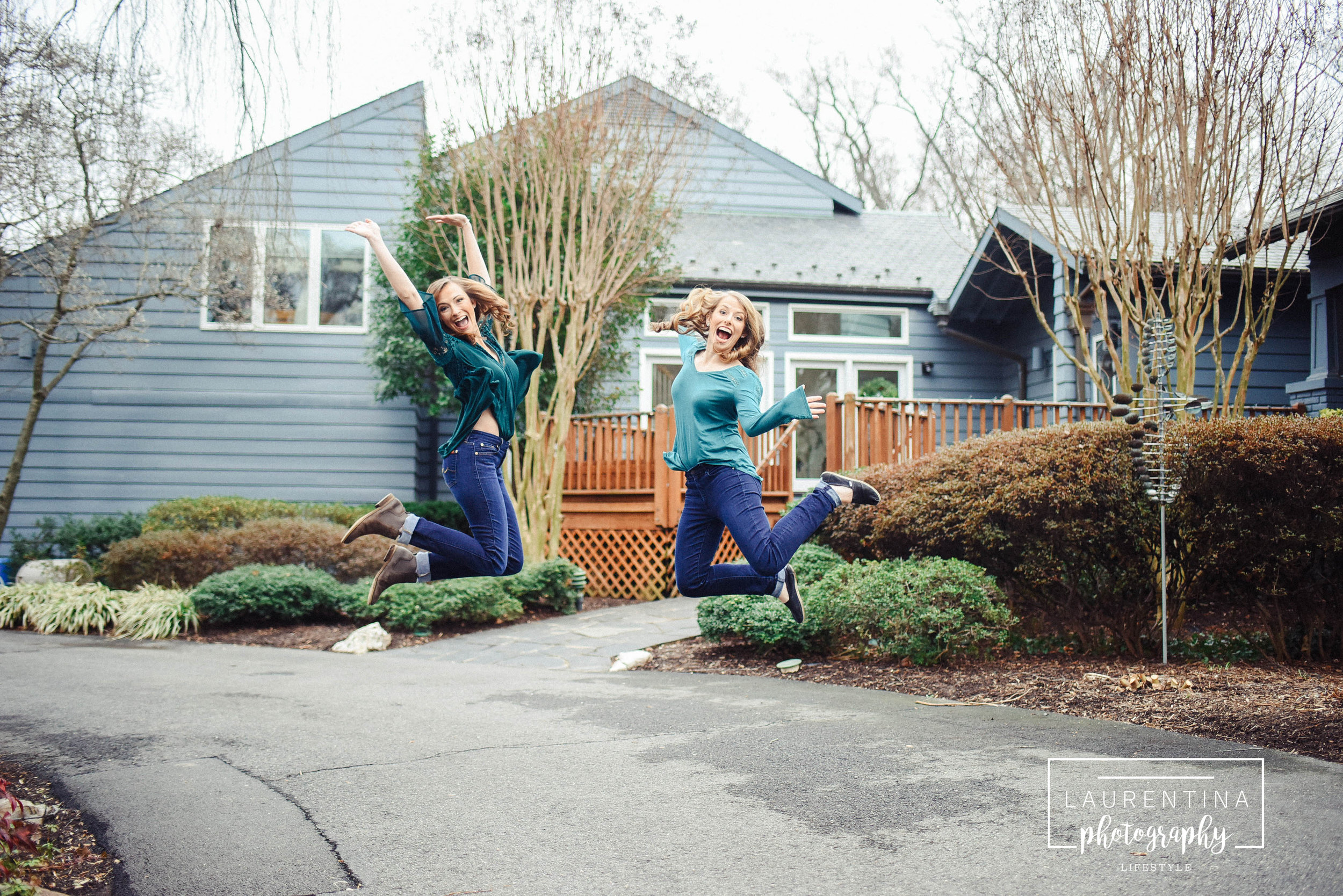 sisters jumping in front of childhood house