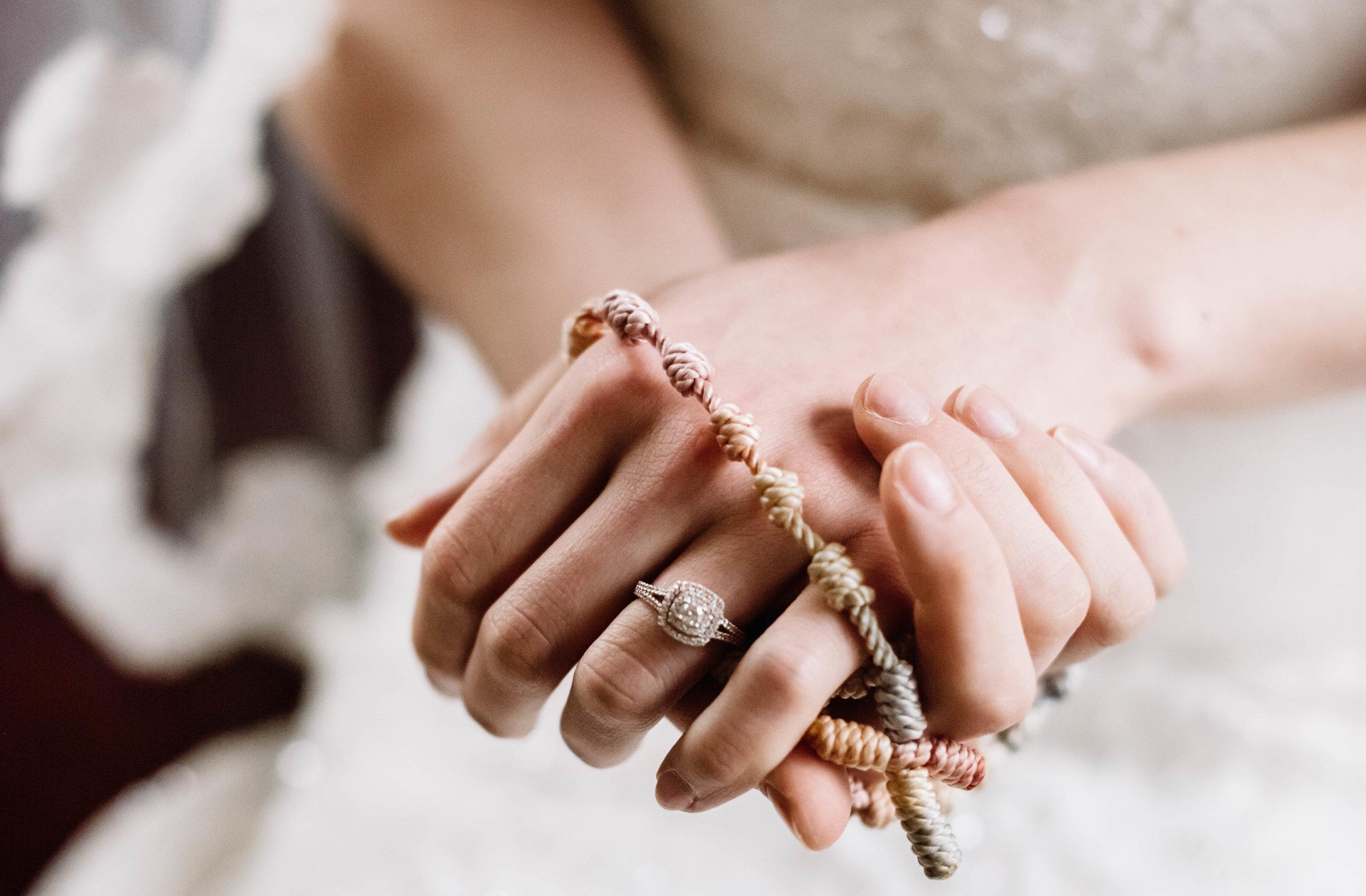 Bride holding rosary wearing wedding ring