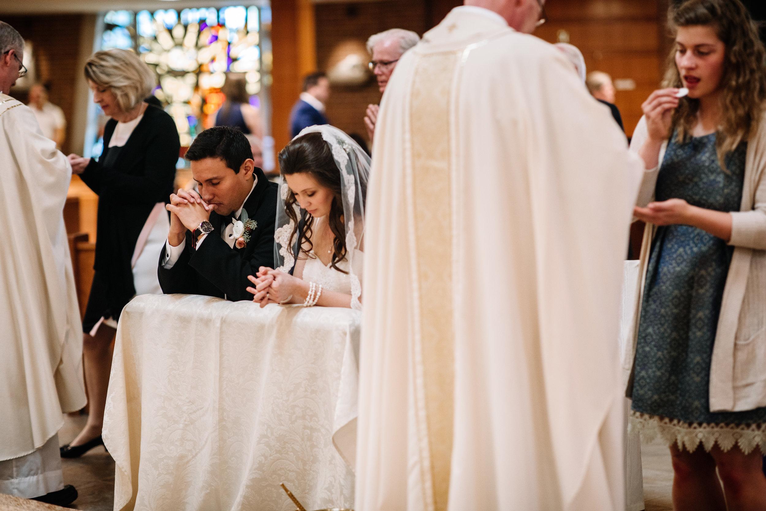 Groom and Bride kneeling Communion Wedding Mass St. Leo the Great Church Fairfax