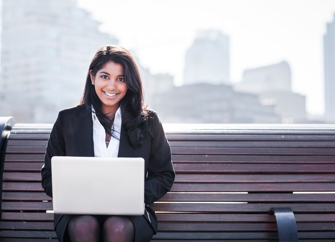 26926247-Pretty-young-woman-holding-a-laptop-standing-by-a-railing-looking-at-camera-smiling-Stock-Photo.jpg