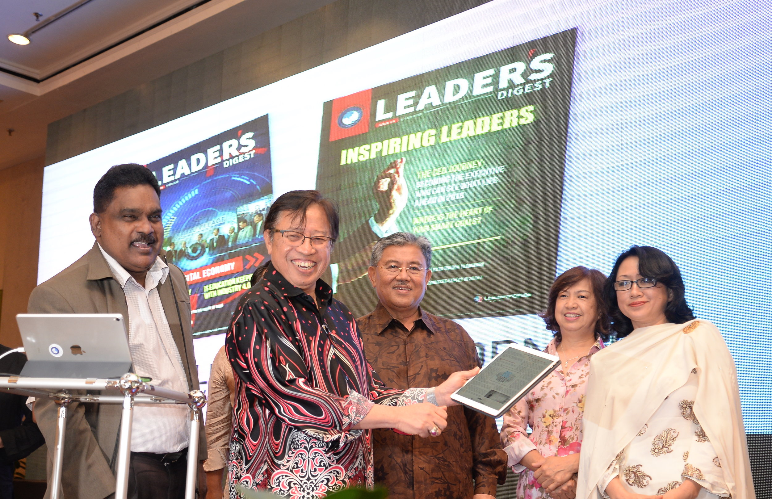Abang Johari taps the tablet to symbolically launch Leader's Digest, witnessed by Morshidi (third right), Sabariah (right), Segaren (on Abang Johari's right) and others.