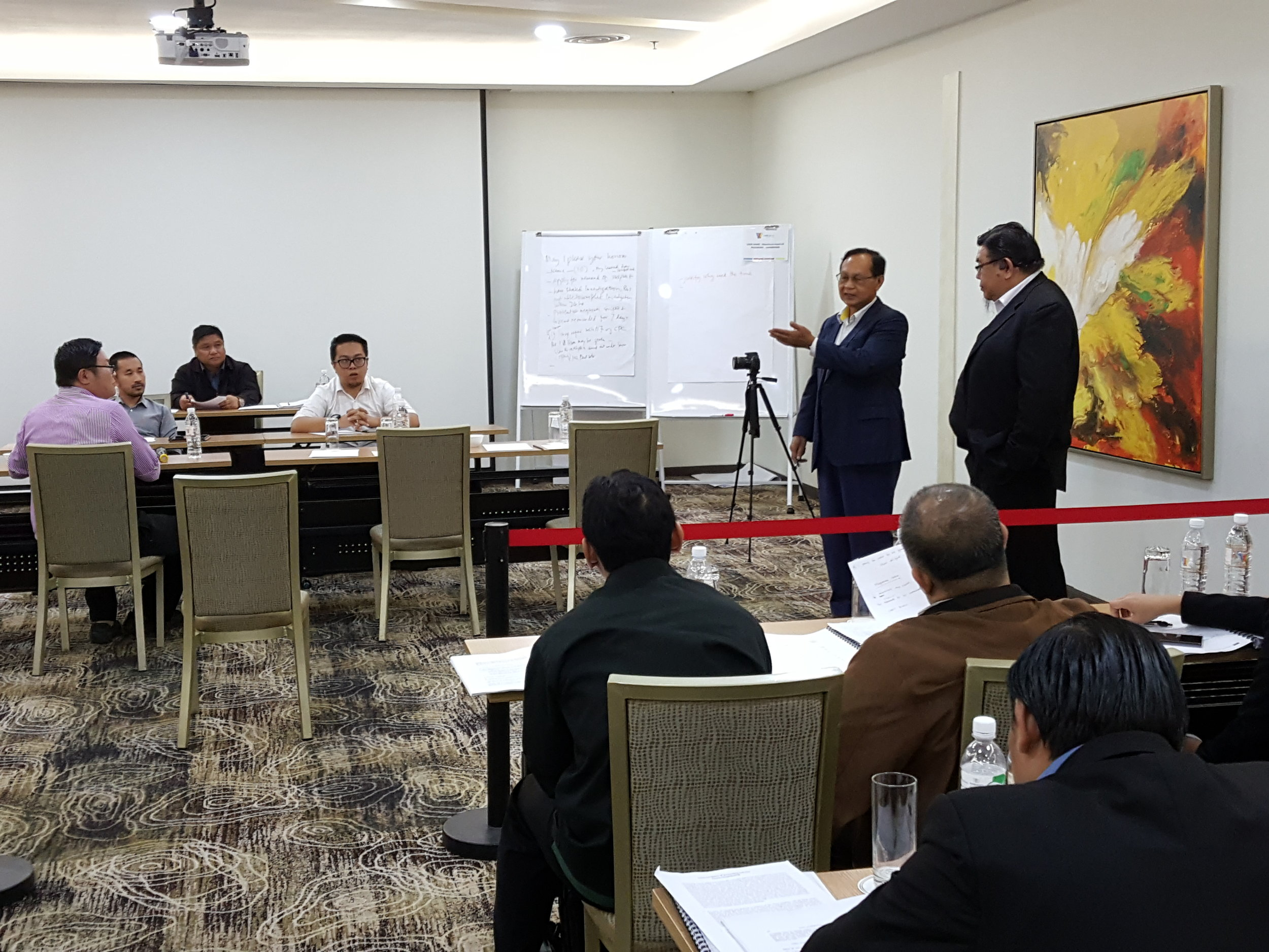 Romie (second right) and Joseph (right) conduct the mock trial simulation during the training programme.