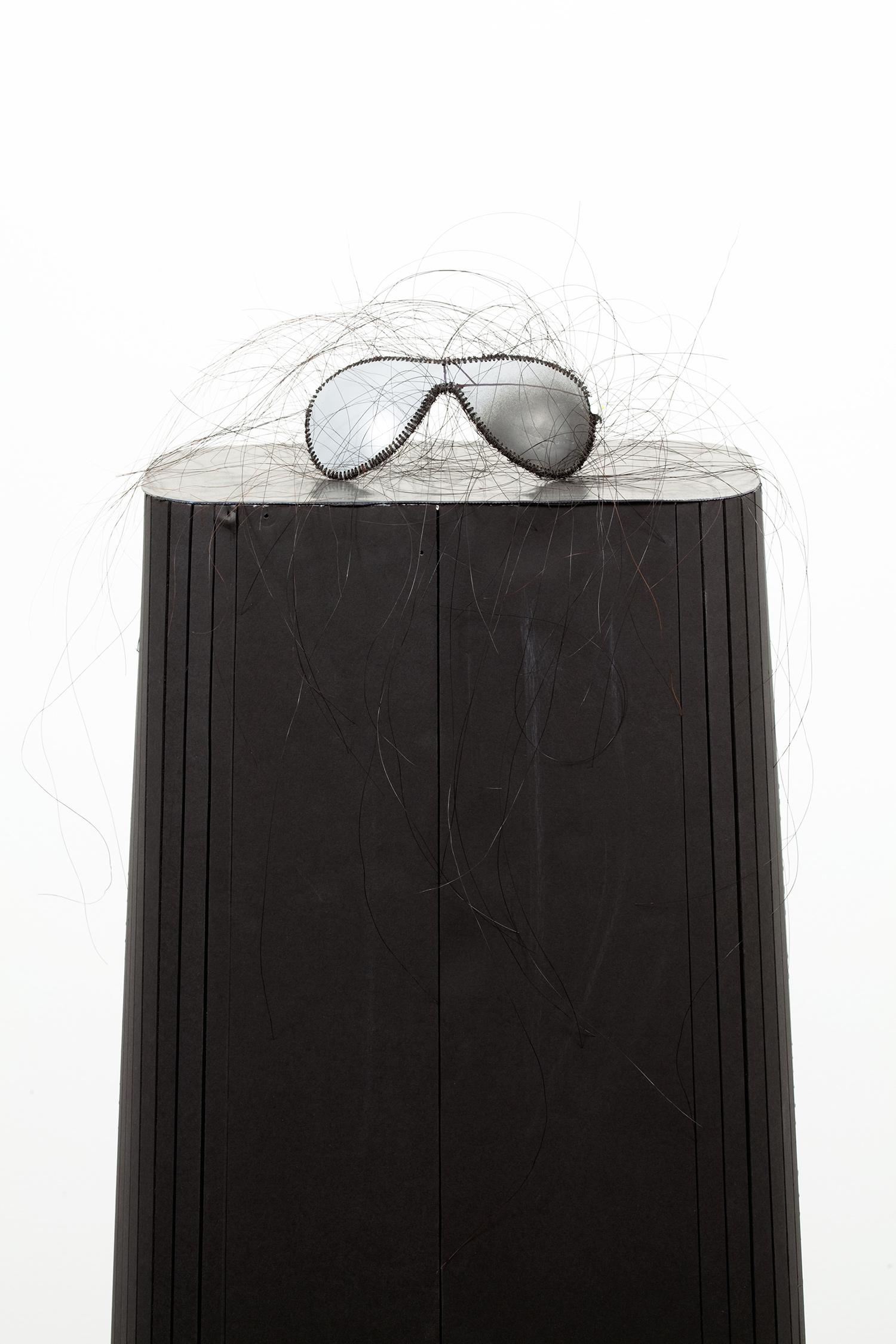 "Trouble. Detail. Horsehair, Labor Boss sunglasses, foam core, lead, stolen, fabric kernel. 55"" x 11.5"" x 6.5"". 2009."