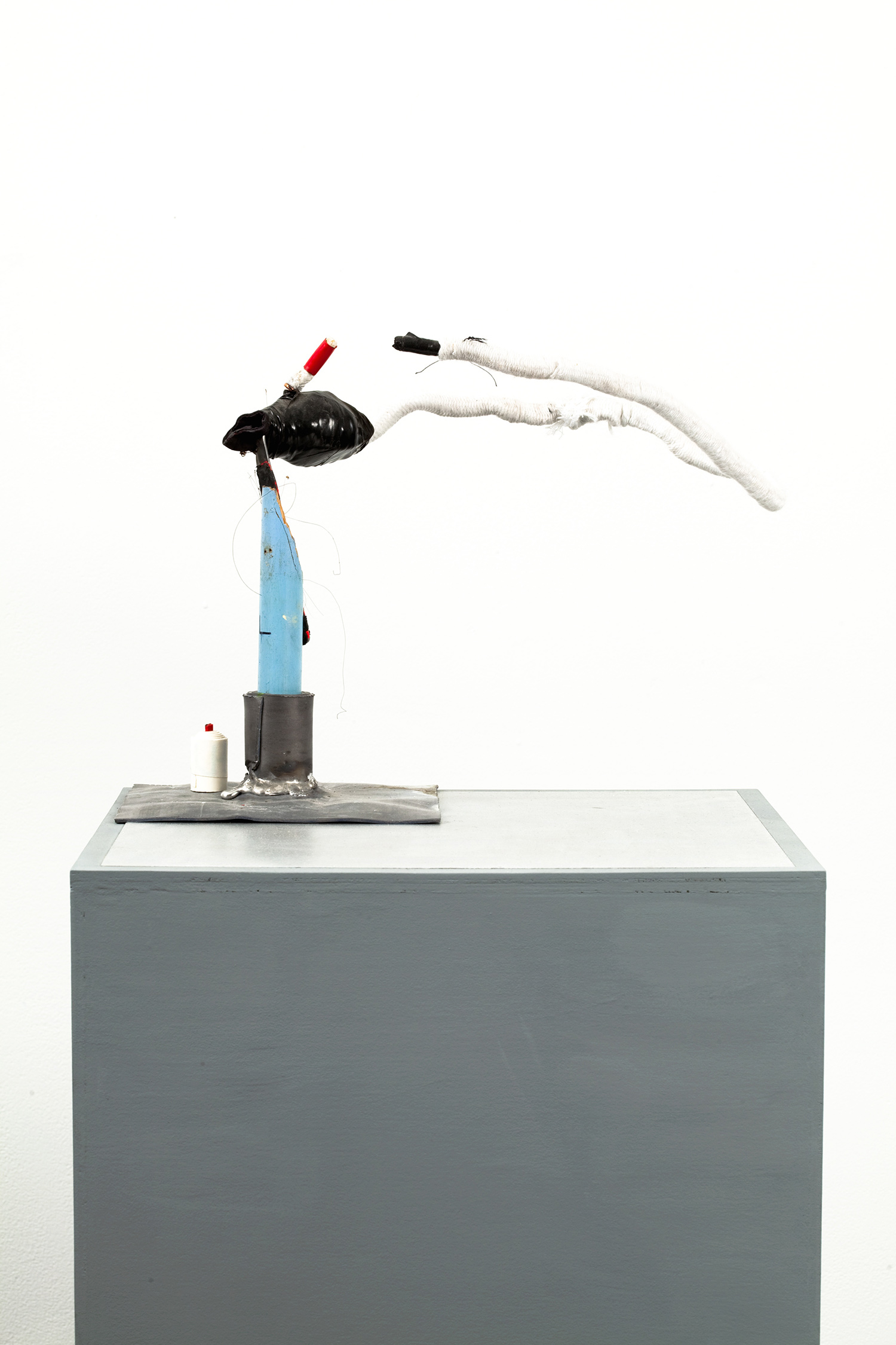 """B.S. Trophy . Detail. Lead, silver spoon, copper, white rope, Resistant's New Kid sleeve, black electric tape, chewing gum, paper. 45"""" x 13"""" x 13"""". 2009."""