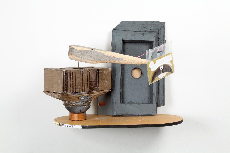 "Middle Management Mustache Prize . Oak, copper, ice pick, cardboard, plaster, brick, pink paper clip, correction fluid, chewing gum. 13"" x 16"" x 9"". 2009."