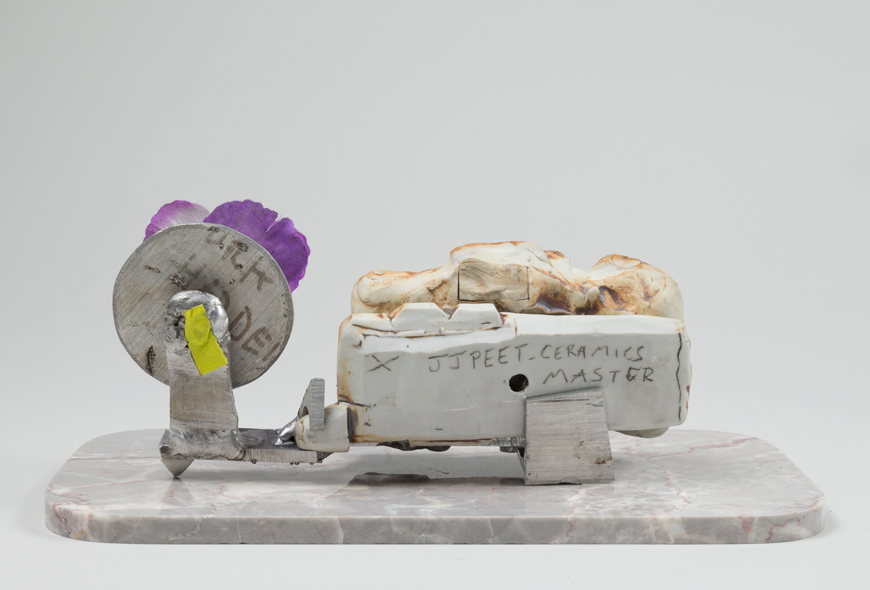 "Machine_Gun_Lover . Porcelain, aluminum, granite, tape, flower. 5"" x 12"" x 5"". 2014."