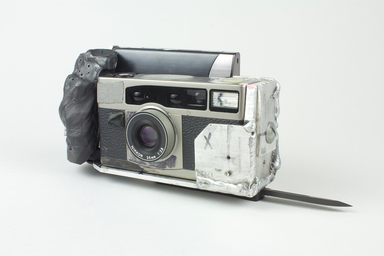 """MACHINE_GUN_VIEWER . Porcelain, aluminum, 35mm bloggy cam, switchblade. 11"""" x 1.75"""". 2014."""