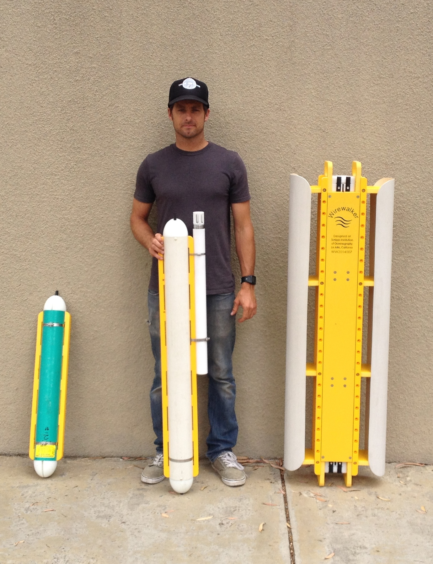 MOD Development engineer, Tyler Hughen, with the three sizes of the Wirewalker wave-powered profiling vehicle.