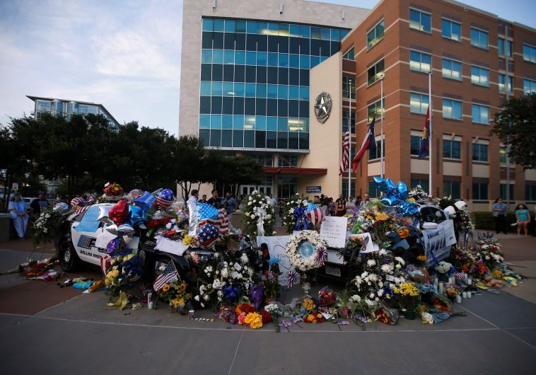 People attend a makeshift memorial at Dallas Police Headquarters following the multiple police shooting in Dallas, Texas, U.S.,July 8, 2016.(photo credit:REUTERS)