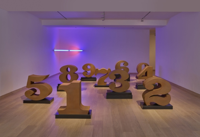 Installation view of  Found in America  with works by Robert Indiana, 'ONE through ZERO' (2003) and Dan Flavin, 'Untitled' (1969). Image courtesy of the Waddington Custot gallery