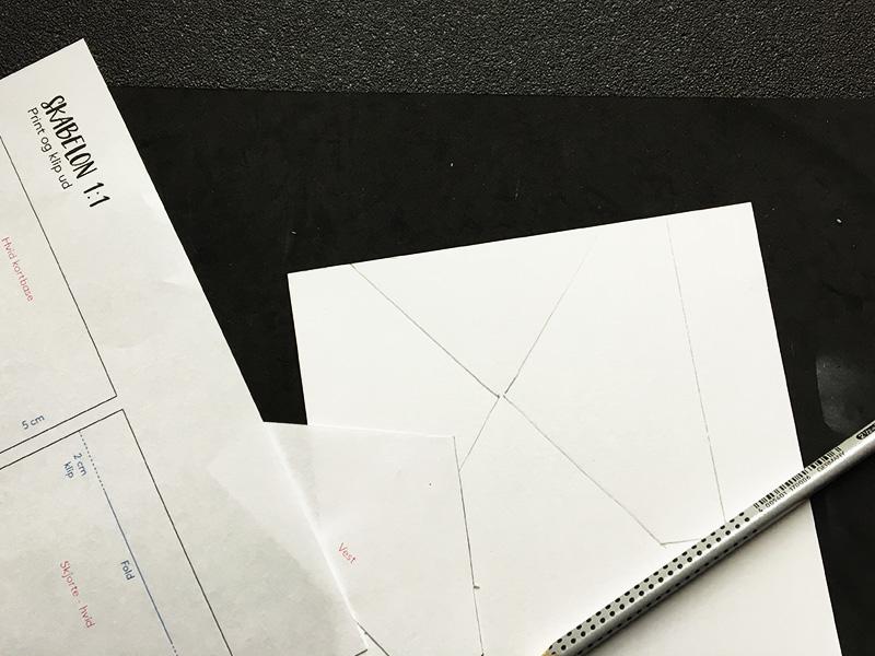 Step 6:  Skær vesten i dit valgte designpapir. Brug skabelonen eller mål selv ud. Her har jeg brugt skabelonen og tegnet den bag på mit papir. Derefter har jeg brugt min skæreplade til at skære efter stregerne. Jeg har brugt Three Scoops designpapir med sorte v'er. Papiret kan du finde i shoppen   her  .