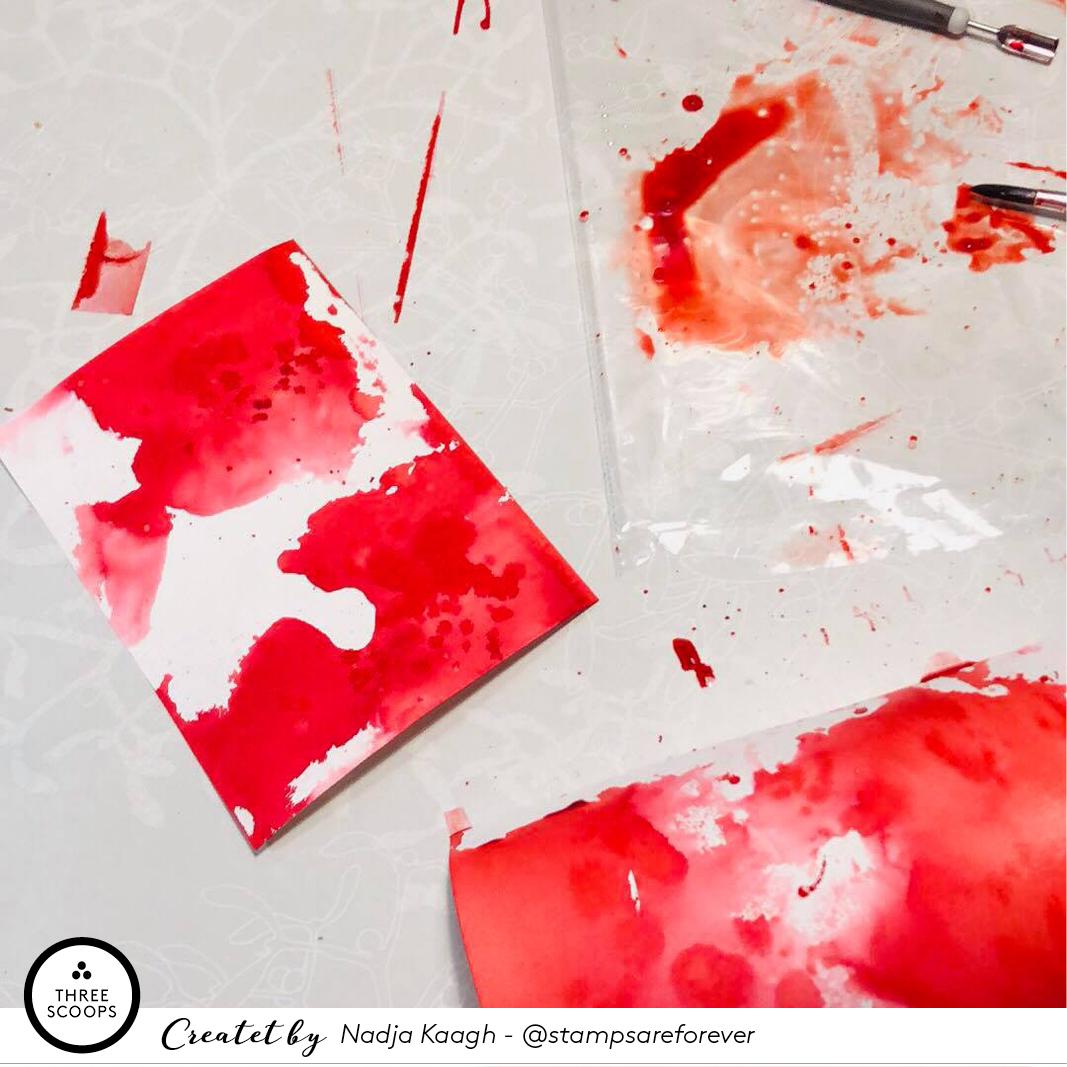 STEP 1:  Jeg starter med at lægge noget rødt sværte, blæk eller vandfarve på et stykke plastik og tilføje vand. Her har jeg brugt en ukendt flydende vandfarve jeg fandt i skabet, men jeg kunne lige så godt have trykket mine vandbaserede Distress eller Distress Oxide puder mod plastikken og tilføjet vand til den sværte der bliver siddende. Herefter lægger jeg mit  akvarel papir , direkte ned i min store farvepøl. Præcis hvordan farven lægger sig på mit papir gør ikke så meget, det vigtige er bare at det fylder godt. Er jeg ikke tilfreds med første dyp gentager jeg og tilføjer evt. splat med en pensel. Mine baggrunde her har fået både masser af dyp og splat med både den røde farve og vand. Det er et forfærdeligt svineri og baggrundene er bestemt ikke pæne alene, men det skal de nok blive!