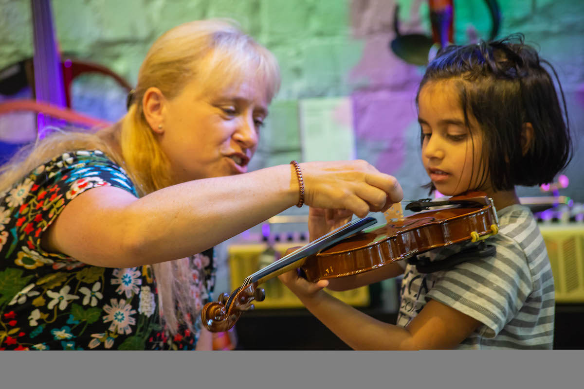 Girl being taught violin at Yamaha Music London Learn to Play Day.jpg