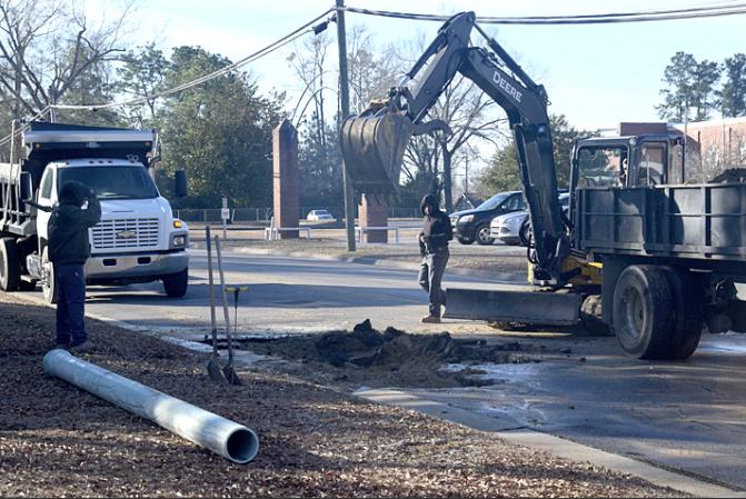 Garrett Bullock, Jaquan Jones and Ethan Dudney work at the site of the water line break on Lee Street.