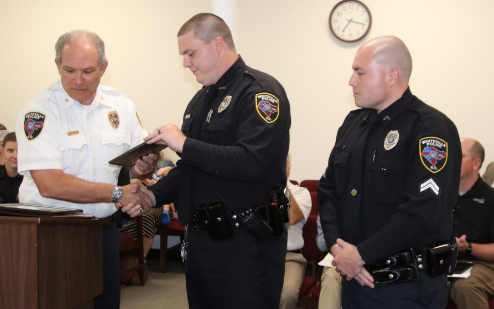 """Police Chief Jeffrey Rozier, left, presented officers Mark Corder, center, and Jonathan Rawls with citations during Tuesday's city council meeting for what he termed """"professional and heroic"""" actions after an armed robbery in May."""