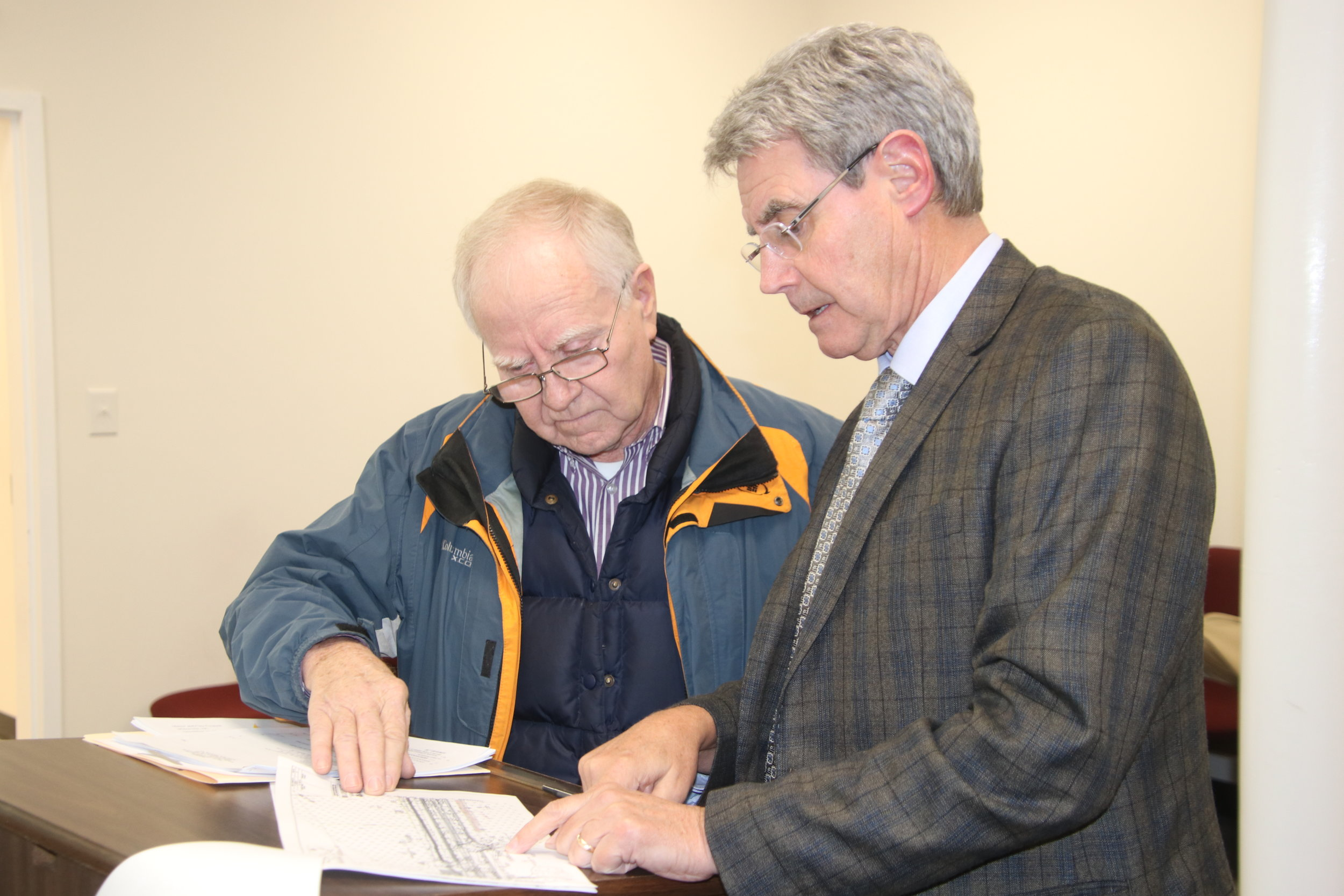 Whiteville City Attorney Carlton Williamson, right, explains the details of a proposed sale of city property to the N.C. Dept. of Transportation to Jim Mauldin during Monday's city council meeting.