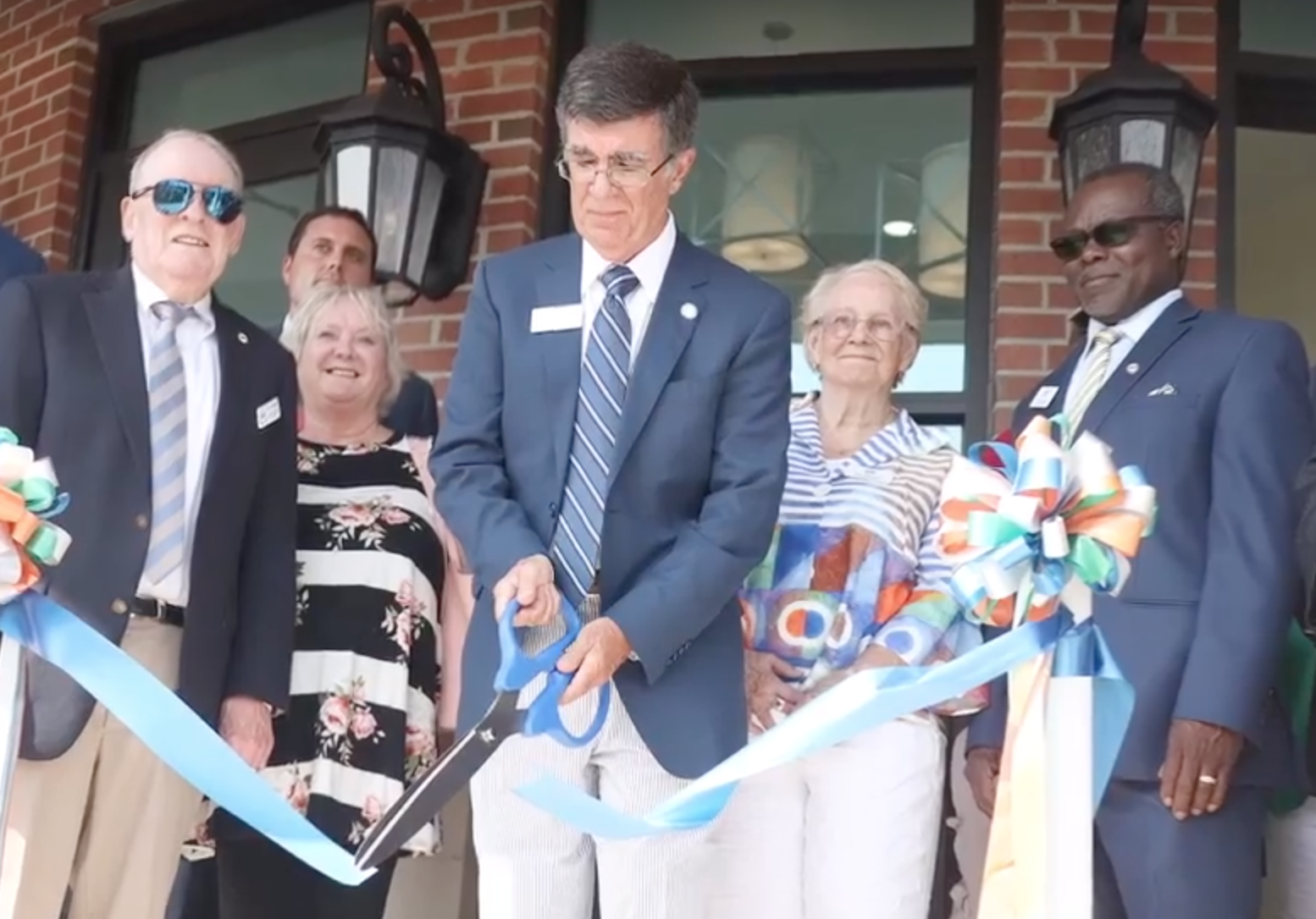 Surrounded by members of city council and other officials, Mayor Terry Mann cuts the ribbon at the new Whiteville City Hall Wednesday afternoon. (Photo by Grant Merritt)