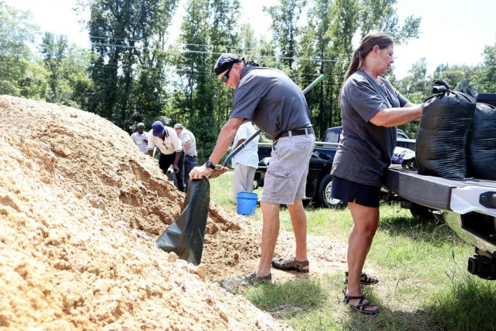 Mitch Hedrick and Grace Mishoe fill sandbags at the City of Whiteville lot off Mill Street Tuesday afternoon.