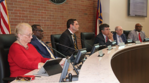 From left, council members Sara Thompson, Jimmy Clarida, Justin Smith, Mayor Terry Mann, Robert Leder and Tim Collier listen to speakers favoring and opposing a zoning ordinance text change that would have permitted an electronic sign at the Whiteville Assembly of God.