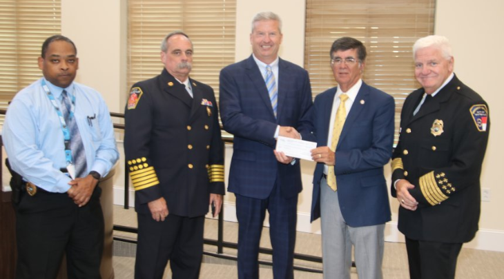 Duke Energy's John Elliott presents Mayor Terry Mann a check from the Duke Foundation for $49,600 Tuesday night as representatives of the city's first responders look on. Pictured, l-r, Interim Police Chief Andre Jackson, Fire Chief David Yergeau, Elliott, Mann and Safety and Risk Management Director Hal Lowder.