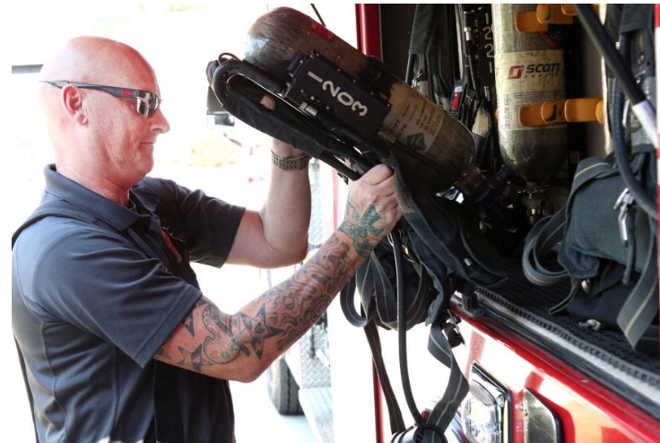Captain Mark Rowan checks air packs on a fire truck during a routine inspection of equipment.