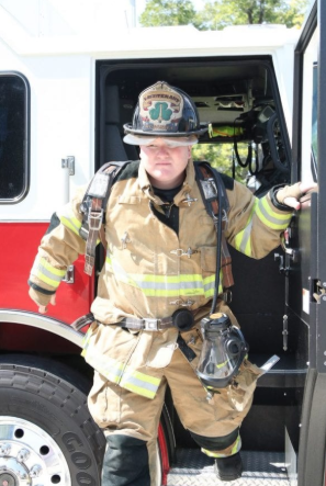 Lieutenant Kyle McDaniel, dressed in full gear, exits a fire truck. Total cost of turnout gear and air packs for one firefighter is about $10,000.