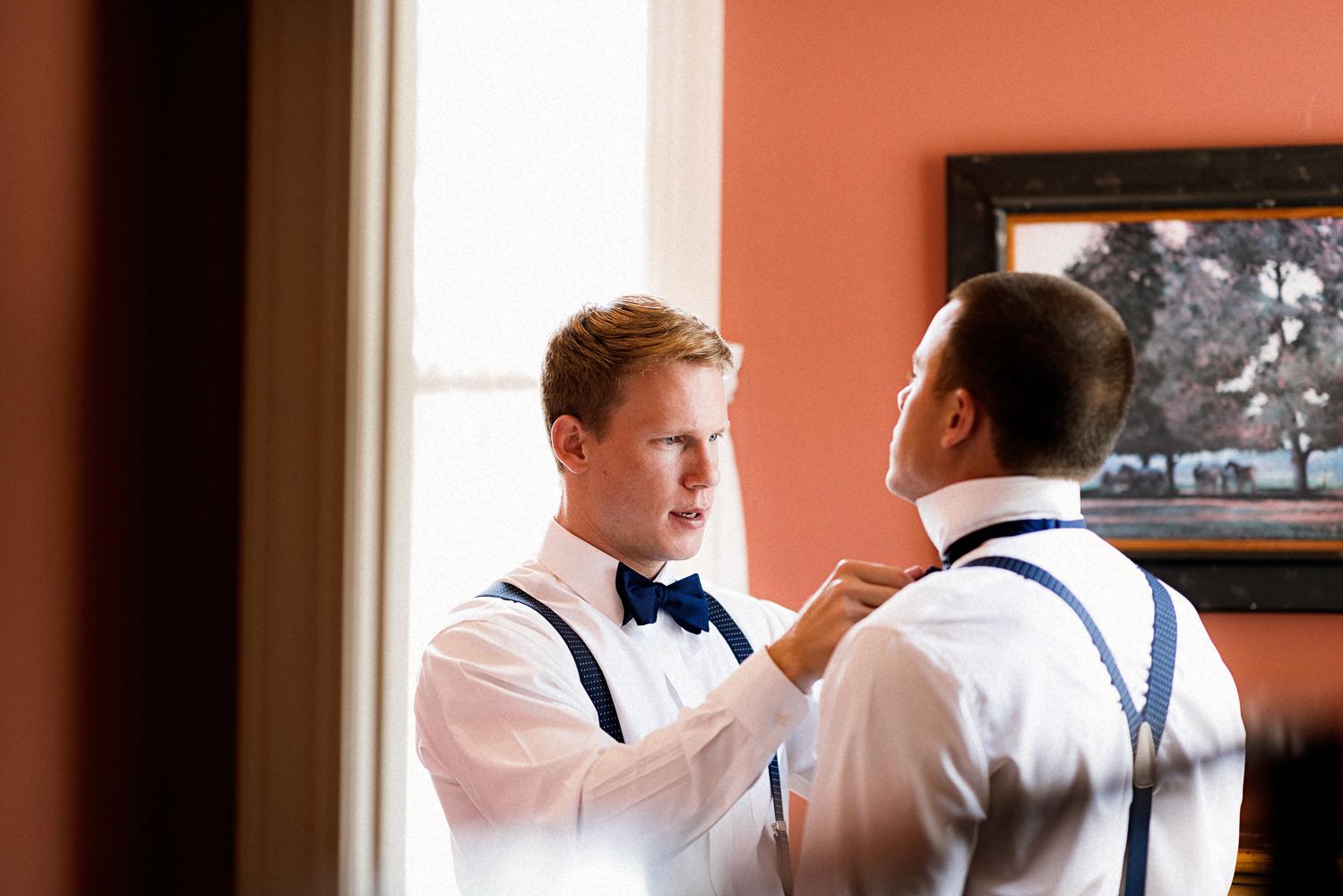 Groom helping his groomsmen get ready.