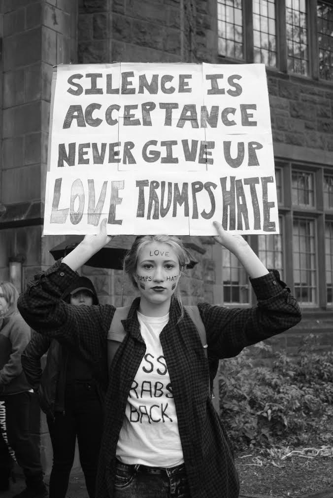 Photo by Leah Willingham '17 Cara Metivier '19 holds up a sign in response to the election of Donald Trump as the president of the United States.