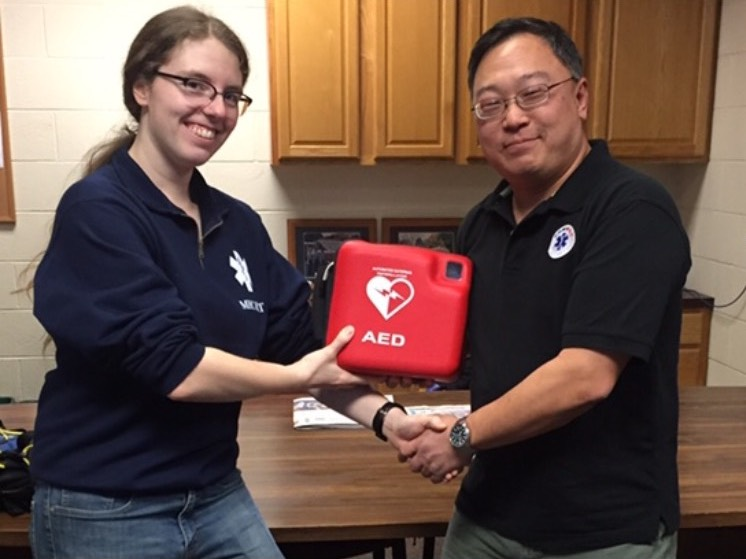 Photo courtesy of MERT  Director of MERT, Louise Tanner '19, accepts a new AED from Dr. Tae Kim, a local medical director.