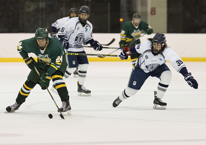 Sophomore forward Arthur Gordon tries to take the puck from a SUNY Oswego Lakers defenseman, while senior forward Jack Ceglarski prepares to help out. The Knights tied the Lakers in a tense and exciting game at the Ira S. Wilson arena on Jan 21. (Annalee Bainnson/Assoc. Photo Editor)