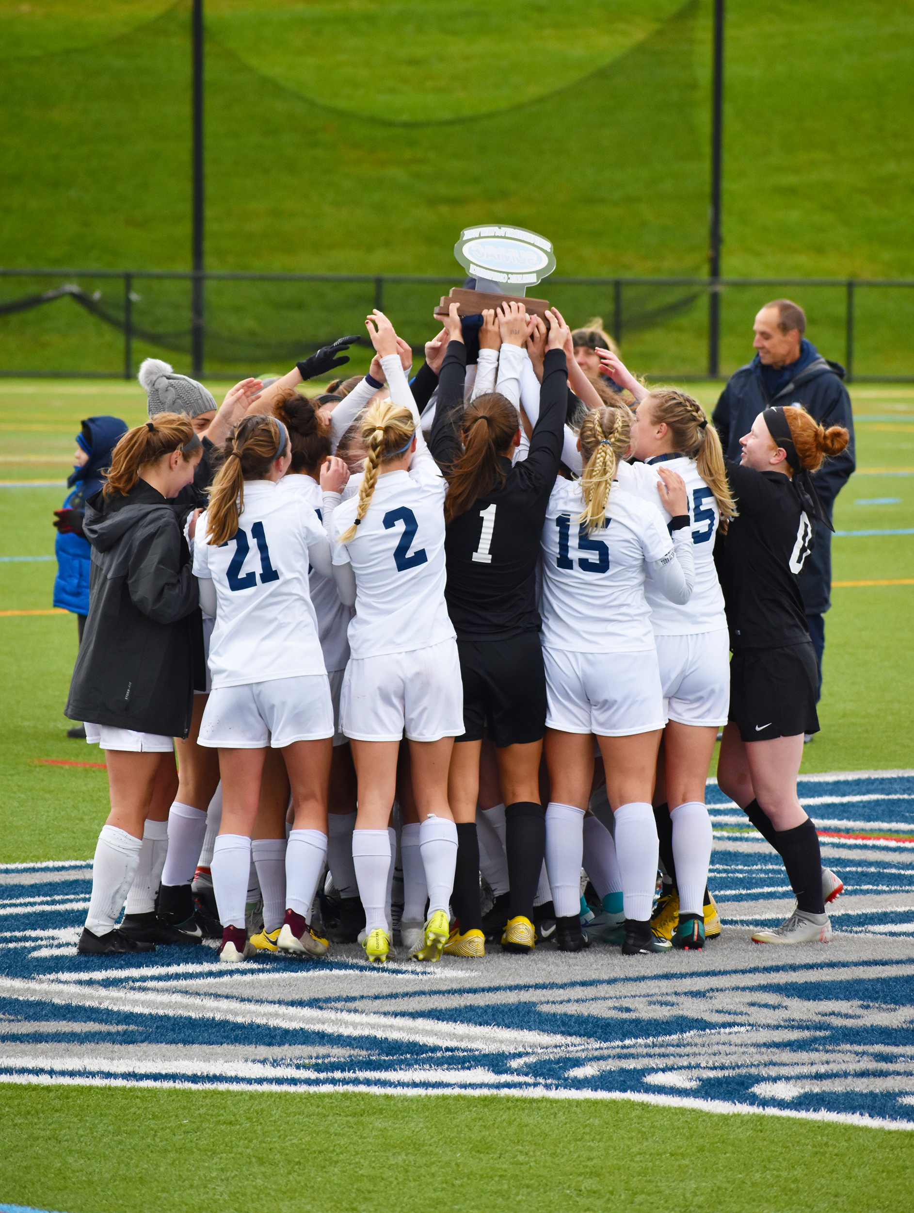 Geneseo women's soccer lifts up the trophy they received for winning their second straight SUNYAC championship (pictured above). The women defeated Cortland 1-0 in the championship game at home on Saturday Nov. 3. The victory ensured the team a spot in the NCAA tournament (Josie Kwan/assoc. photo editor).
