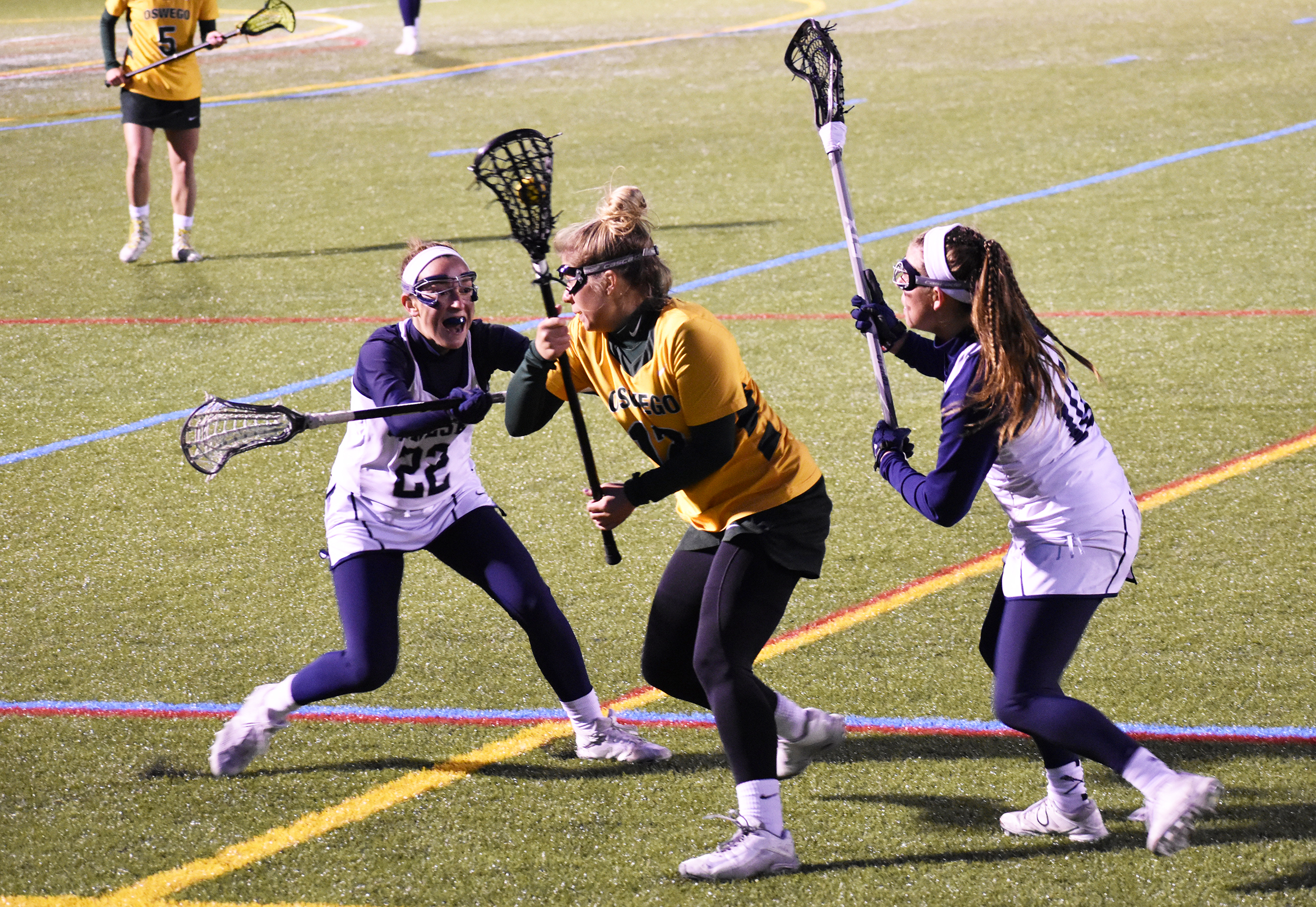 Junior midfielder Tessa Doody and junior defender Cassidy O'Rourke team up to defend an Oswego midfielder. Geneseo defeated Oswego 13-11 on Wednesday April 10 (Josie Kwan/Assoc. Photo Editor).