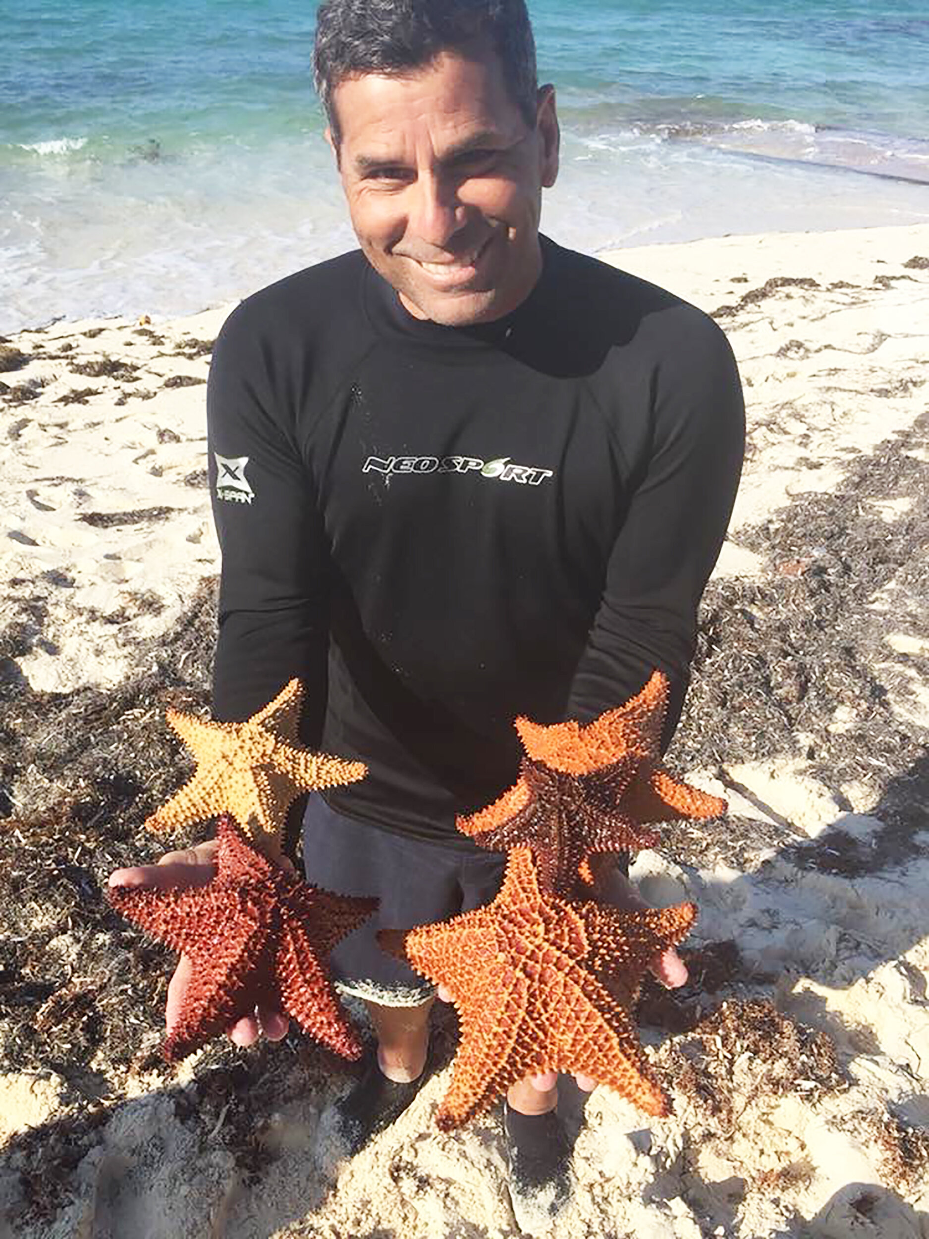 Biology professor Isidro Bosch (pictured above) displays his love for the ocean, holding a series of starfish in his hands. Bosch also has a passion for Antarctica, where he has conducted research and taken students on study abroad trips (courtesy of Isidro Bosch).