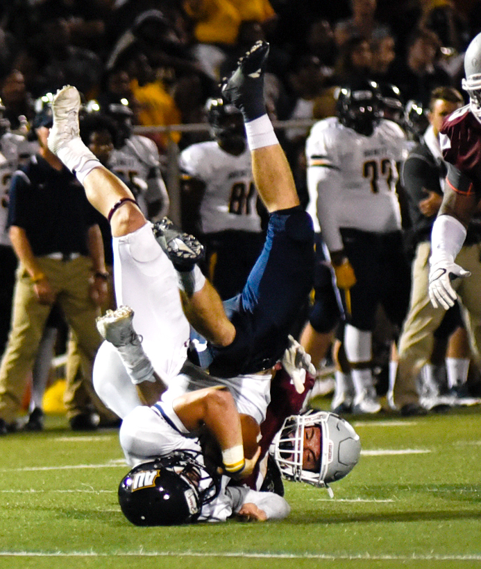 Averett's Kelly Hall (right, 5), flips with the ball from a tackle by Guilford's Robert Smith (left, 4) on Saturday, September 19, 2015.