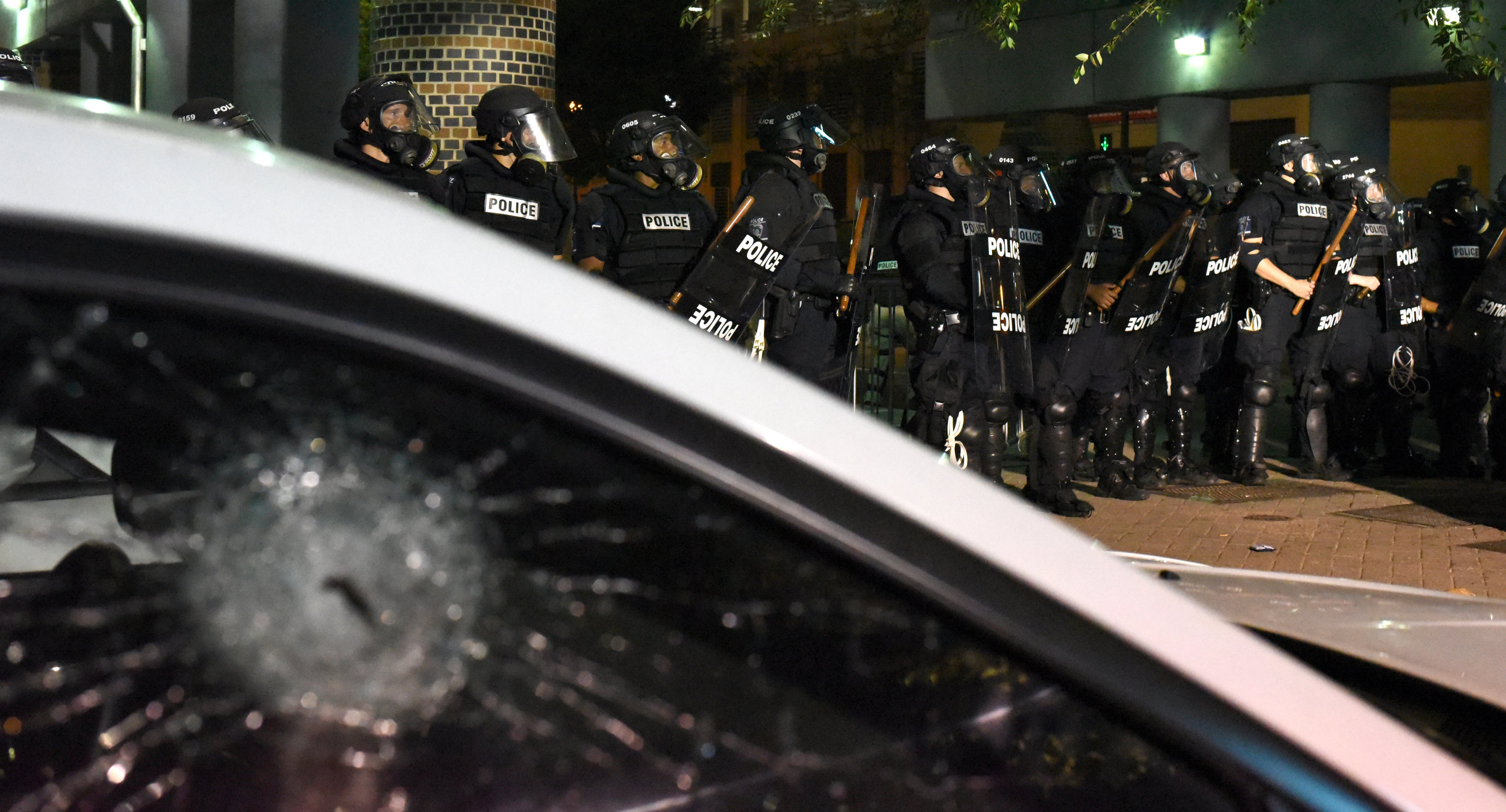 Riot police officers stand near an automobile with a smashed window as they confront protestors in Charlotte, North Carolina, USA, 21 September 2016. North Carolina governor Pat McCrory declared a state of emergency after protesters took to the streets of Charlotte, North Carolina, for the second consecutive night to demonstrate against the fatal shooting of African-American Keith Lamont Scott by police officers.