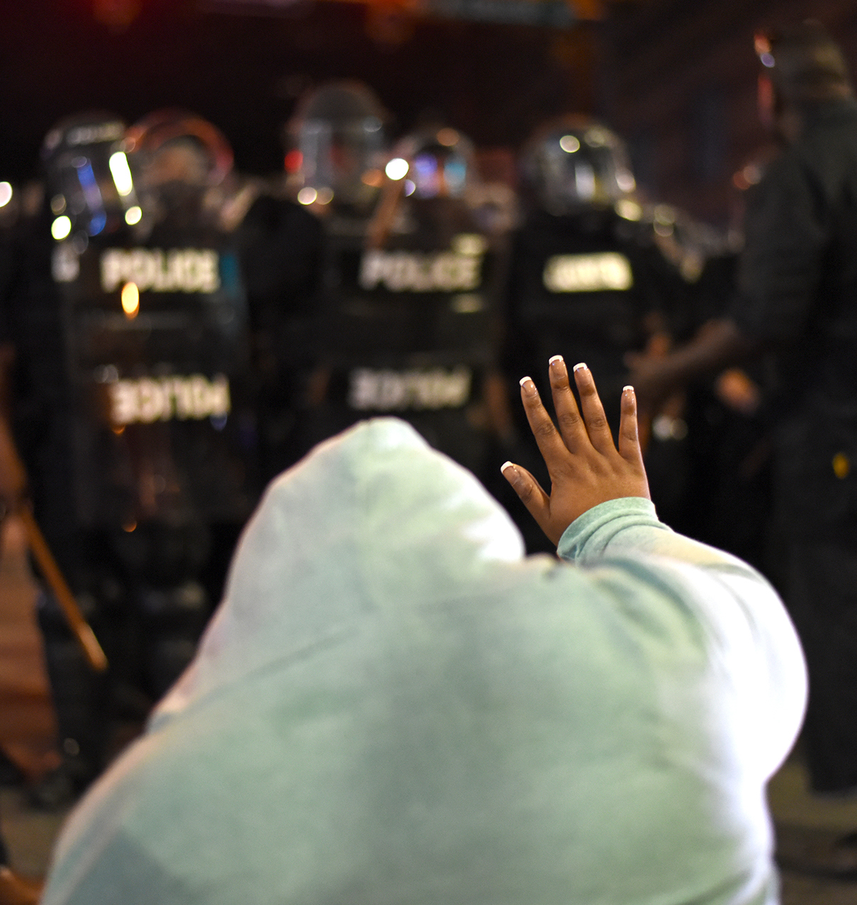A protestor holds up her hand in front of riot police officers in Charlotte, North Carolina, USA, 21 September 2016. North Carolina governor Pat McCrory declared a state of emergency after protesters took to the streets of Charlotte, North Carolina, for the second consecutive night to demonstrate against the fatal shooting of African-American Keith Lamont Scott by police officers.