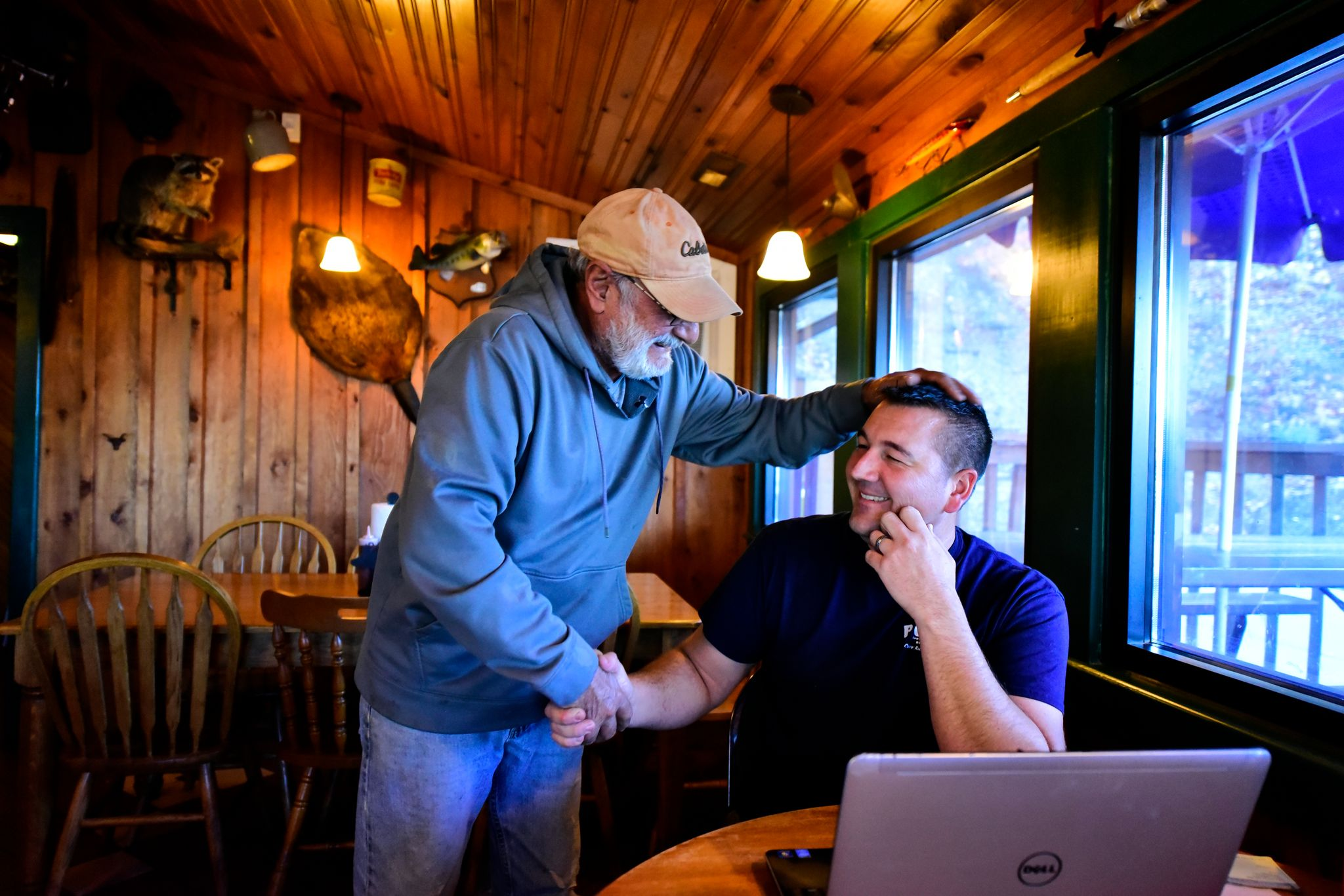 """Mike Winer, left, a Pop's BBQ regular, greets Adam. Adam fosters the values of community and family at Pop's. """"Sometimes he comes in for five minutes to talk, sometimes it's 30 minutes,"""" says Adam."""