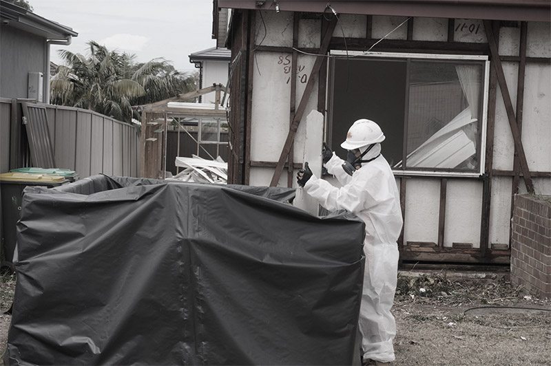 An asbestos removal worker carefully place asbestos in a plastic covered skip.