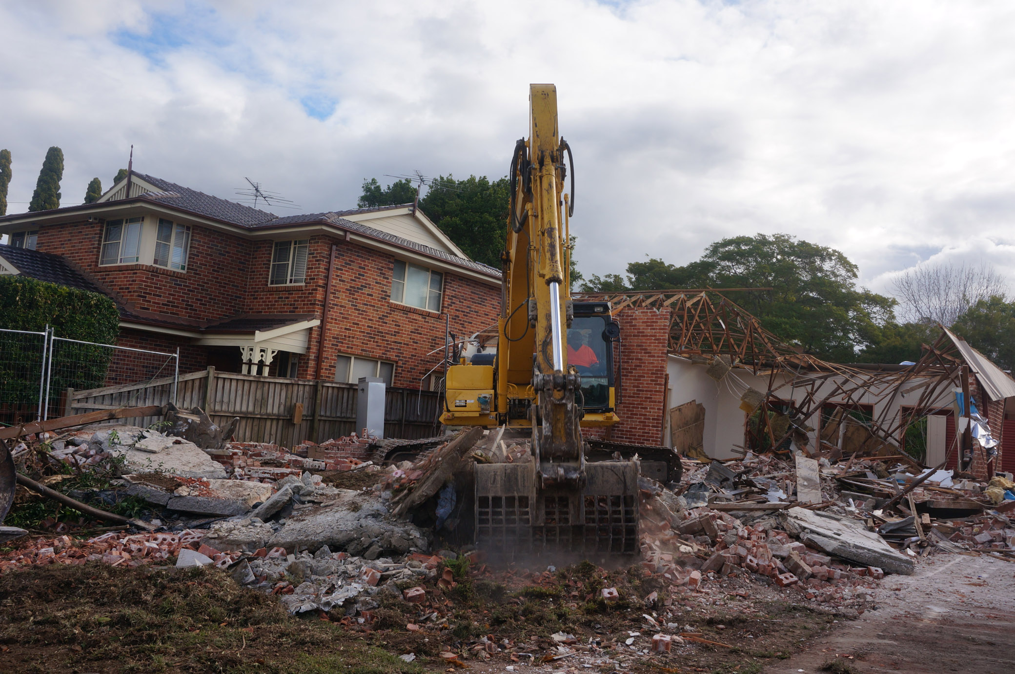 Excavator clearing cement and smashed brick at demolition site in West Ryde.jpg