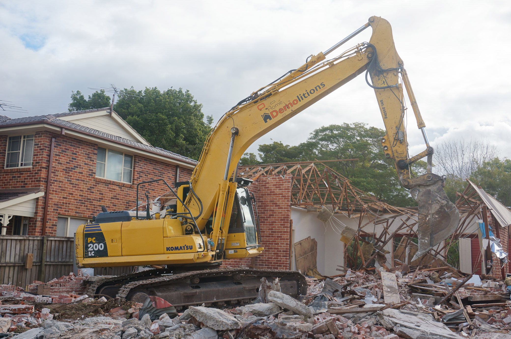 Excavator in front of partially demolished brcik house in West Ryde.jpg