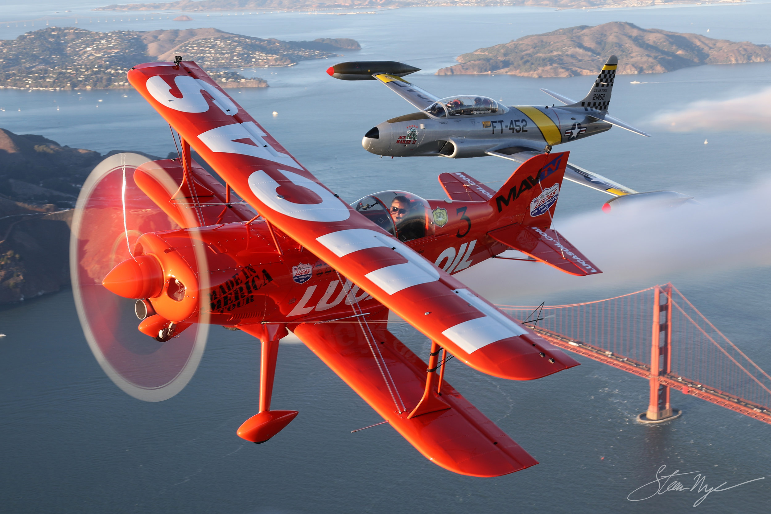 Stunt pilot Michael Wiskus flying his Pitts Special with Greg Colyer's Ace Maker T-33 over the Golden Gate Bridge in San Francisco, CA.