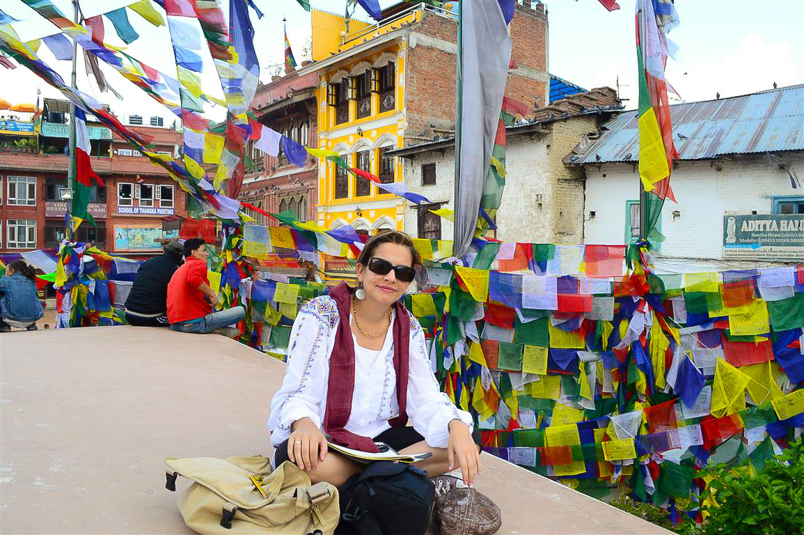 An emblematic view of Juanita and the prayer flags at the Bouddhanath Stupa in Kathmandu, Nepal