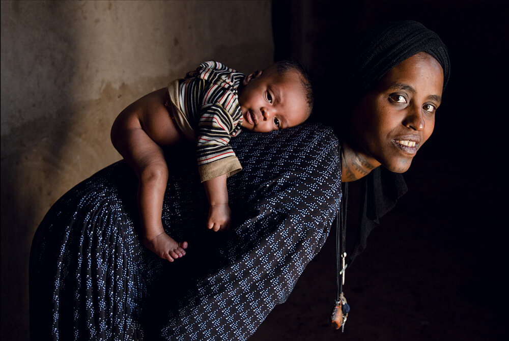 Around the world, the weight of child rearing falls squarely on the backs of women. From carrying the pregnancy and the risks of childbirth to caring the for the child's health and wellbeing in life, women are responsible for ensuring that children have proper nutrition, healthcare, and education.  We met this mother and baby in 2013   Amhara, Ethiopia 2013, Featured in the film Making Pregnancy Safer,: Safe Delivery 2013