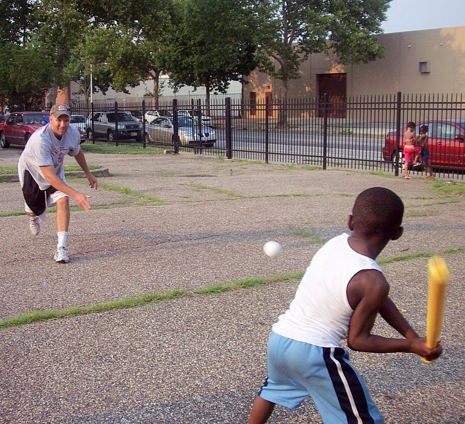 Adam Bruckner playing baseball with boy at The Mission