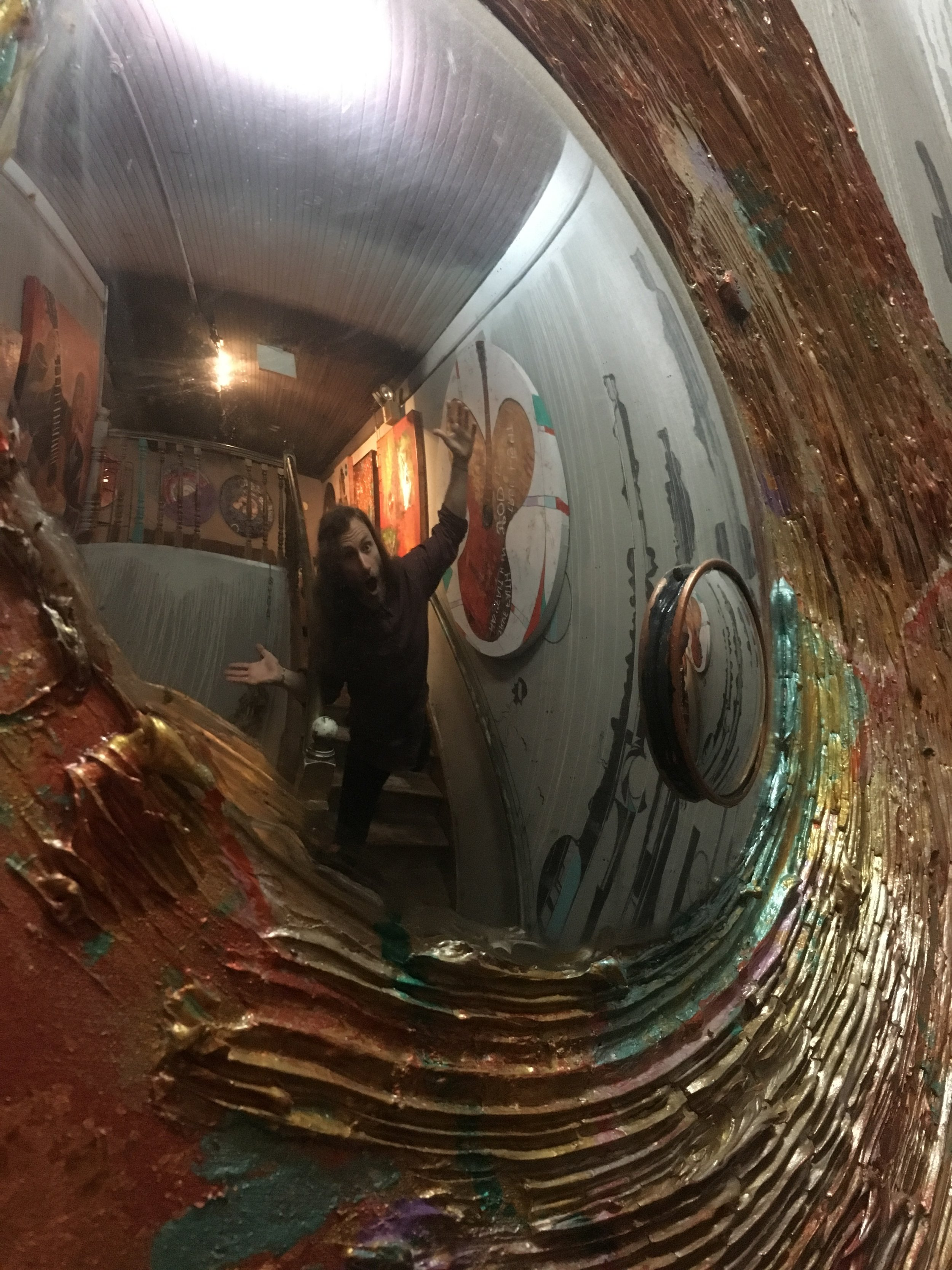 Matt Miller throws up a goofy pose in the mirror of one of his many paintings Friday, Apr. 21, 2017. Mr. Miller completed this specific piece around 3 years ago. It now hangs on display at  Path Outfitters.