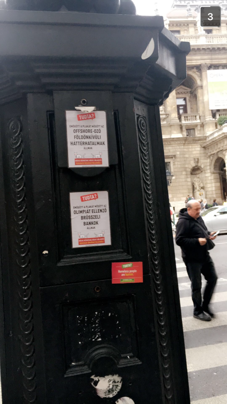 Outdoor sticker placement beside other 'Tudta?' (did you know?) stickers — one of the Hungarian government's anti-immigrant propaganda tools