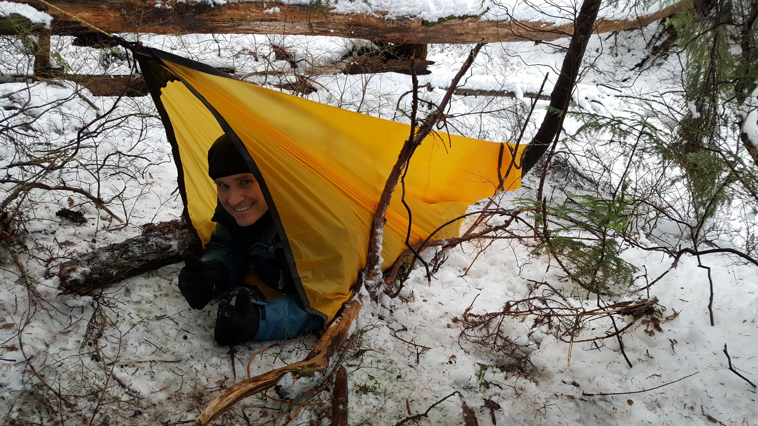 It would be nice to have some padding under me, but my mighty shelter will keep me dry. A bit of snow banked around the sides, and a carefully tended fire near the opening - taking care not to let sparks near my tarp or smoke myself out - will make my night easier.