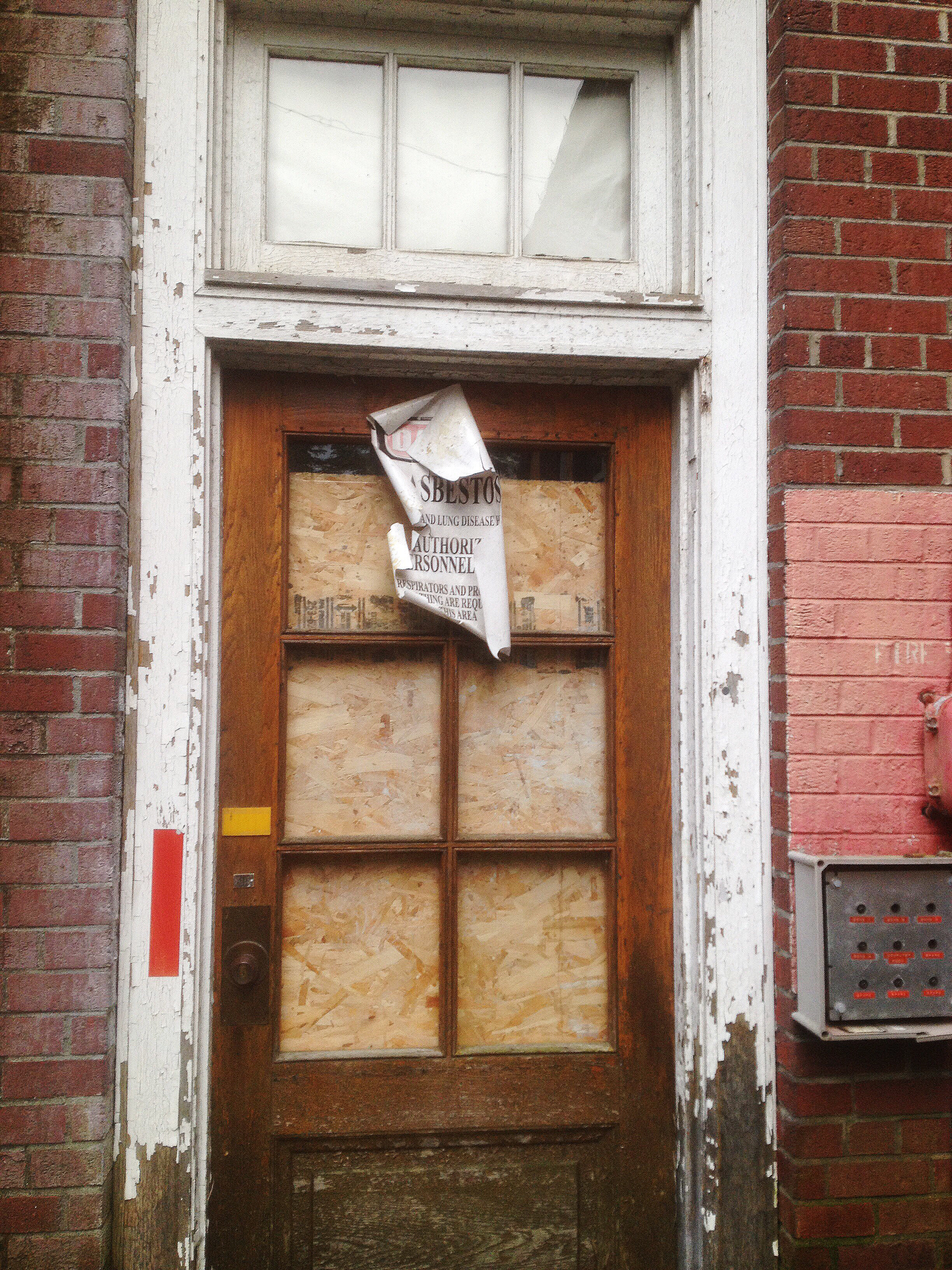 Boarded up exterior door.