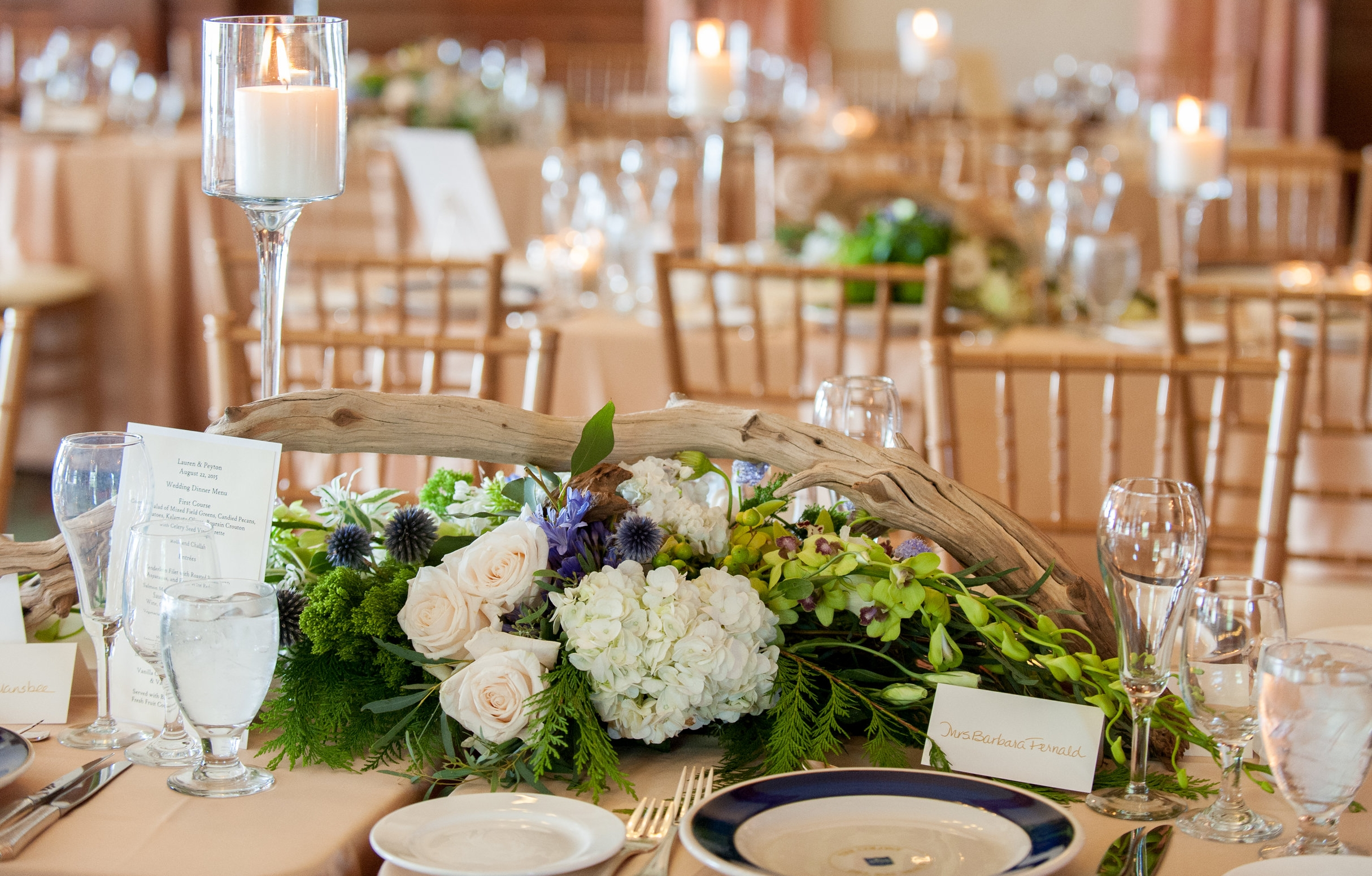 Florals in shades of cream and blue enhanced the bridal bouquet, chuppah, and centerpieces for the main event. Driftwood added a rugged Maine touch to the elegant formal tables.